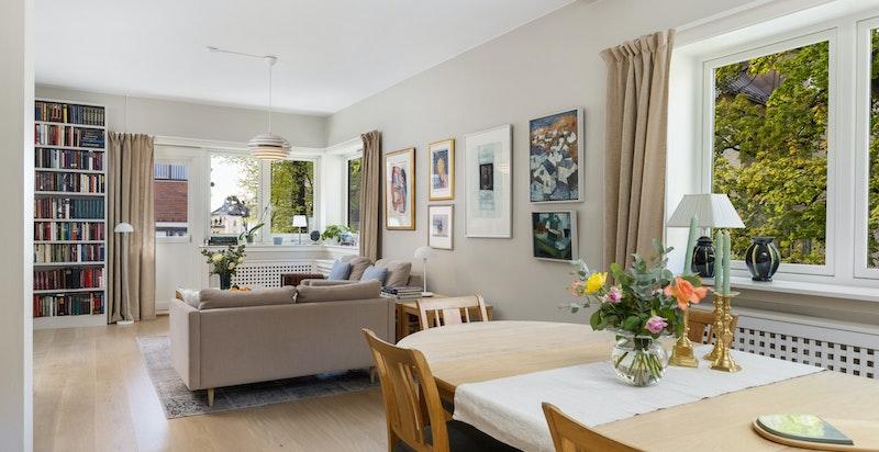 Det er åpen løsning mellom kjøkken og stue og store vindusflter gir mye lysinngang