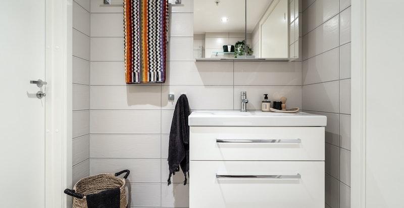 Badet er utstyrt med vegghengt klosett, dushjørne og innredning med servant