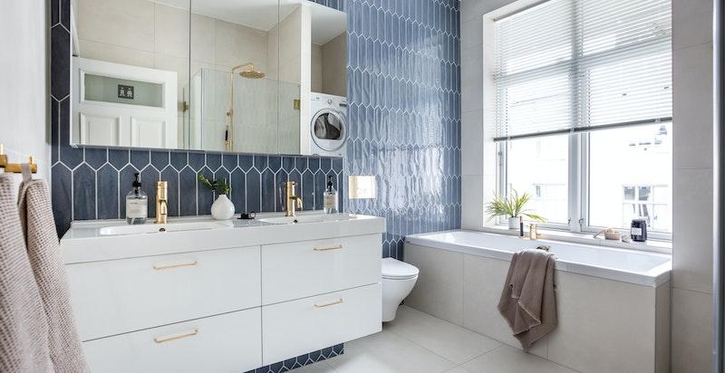 Lekkert baderom fra 2019. Rommet er stort og inneholder både badekar og dusjhjørne.