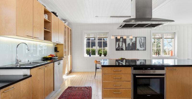Kjøkkeninnredning har fronter av bjørk, benkeplater i sort granitt, glassplate over vask og kokeøy med frittstående avtrekksvifte. Kjøkkenet er stort og det er godt med skap og benkeplass.