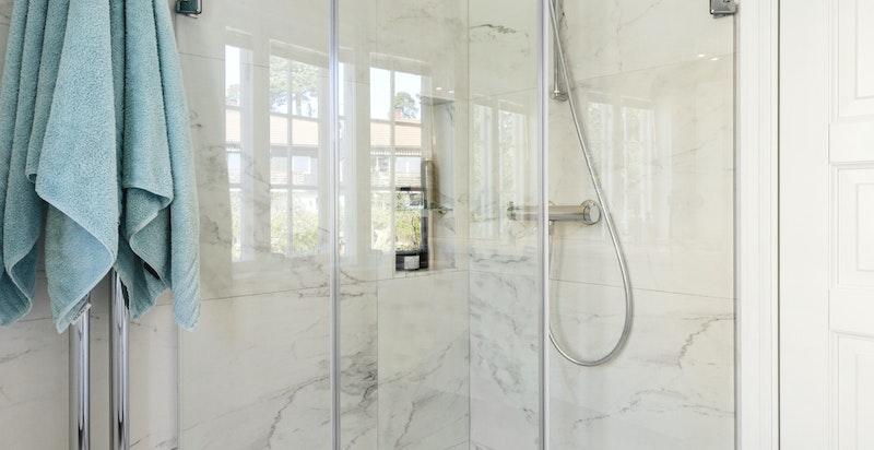 Ekstra romslig dusjnisje med glassvegger og integrert hylle for sjampo etc.