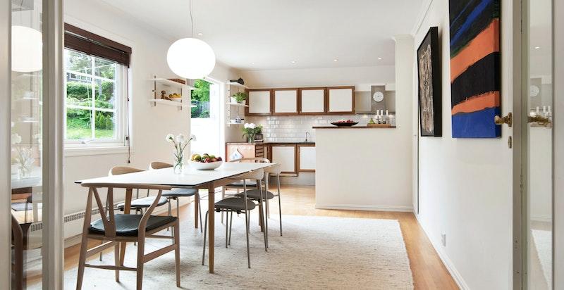 Lys og luftig kjøkkenløsning med spiseplass og utgang terrasse og hage