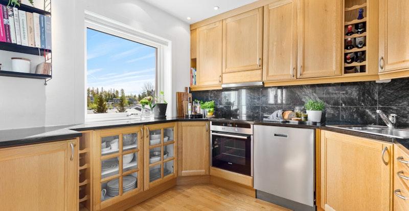Eldre kjøkkeninnredning med eik fronter og granitt benkeplater