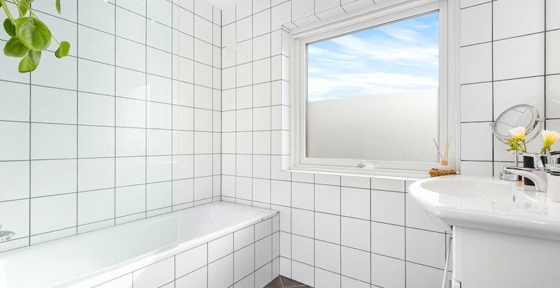 Lyst og tiltalende bad innredet med badekar m/dusj og glassvegg, servantskap og vegghengt toalett