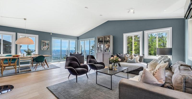 Stor og åpen stue/spisestue med peisovn og panoramautsikt