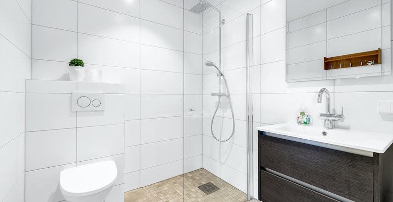 Meget pent flislagt dusjbad/wc med varmekabler i gulv. Nedsenket gulv i dusjnisje. Dusjnisje med glassdør. Vegghengt servantskap og wc med innebygget sisterne. Nedsenket himling som er sparklet og malt. LED downlights