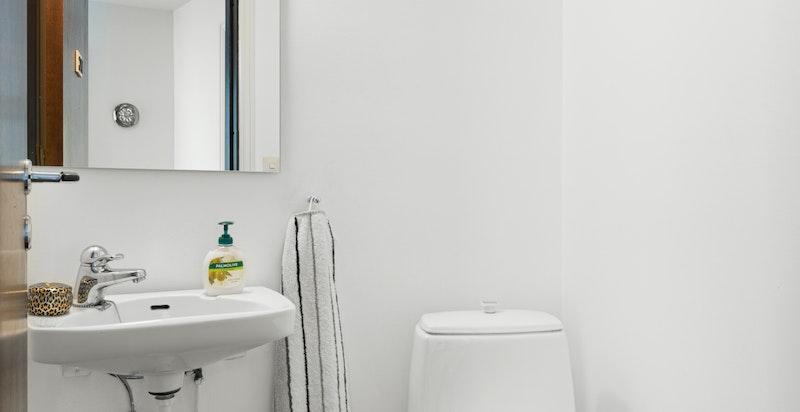 Toalettrom i boligens førsteetasje, rommet er innredet med klosett og servant.