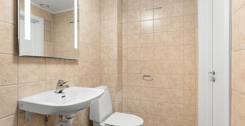 Videre har badet servant, ettgreps blandebatteri, speil med ekstra belysning og toalett.