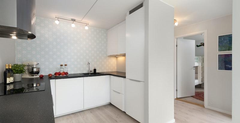 Kjøkkenet er utstyrt med integrert komfyr, induksjons platetopp, oppvaskmaskin og kjøleskap med fryser