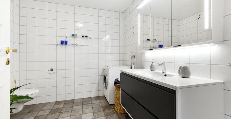 Stort og flislagt bad innredet servantskap, vegghengt toalett og dusj med glassdør