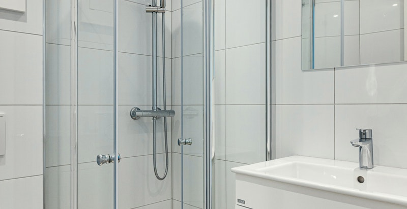 Vegghengt toalett og dusjhjørne med innfellbare dusjvegger i herdet glass.