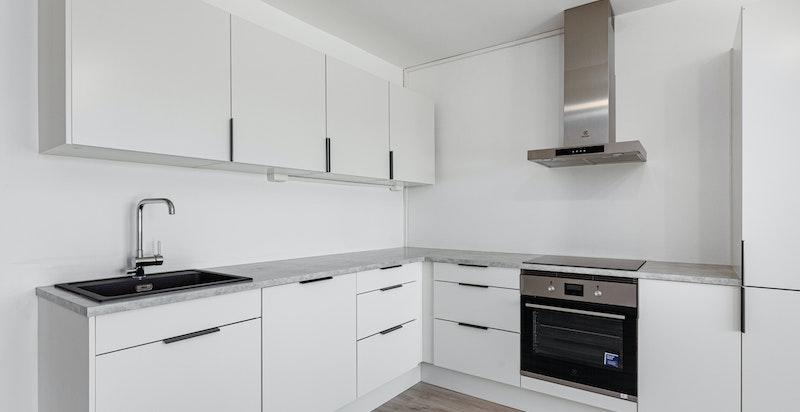 Kjøkkenet er levert fra HTH med hvitefronter og grå laminat benkeplate i lekker kombinasjon.