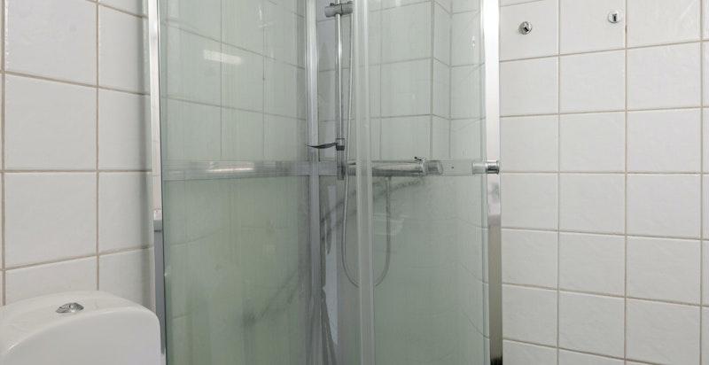 Badet er innredet med dusjkabinett, servantskap og toalett