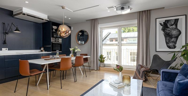 Flott spisekjøkken / stue med brede en-stavs gulv og fransk balkong med store vindusflater