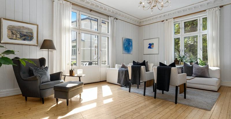 Hjørnestue med lysinnslipp fra flere vinduer gjør leiligheten lys og koselig