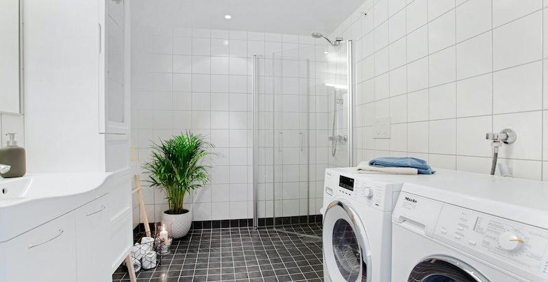 Innholdsrikt og romslig bad i moderne lekker utførelse. Plass for sidestilt vaskemaskin og tørketrommel.