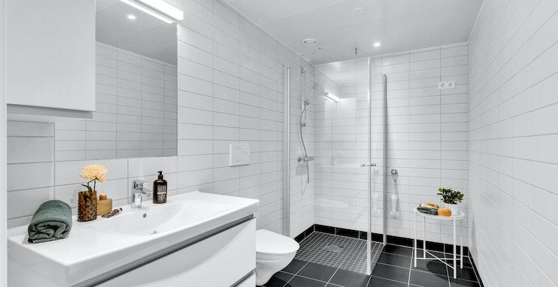 Flislagt bad med servant, vegghengt toalett og dusjnisje.