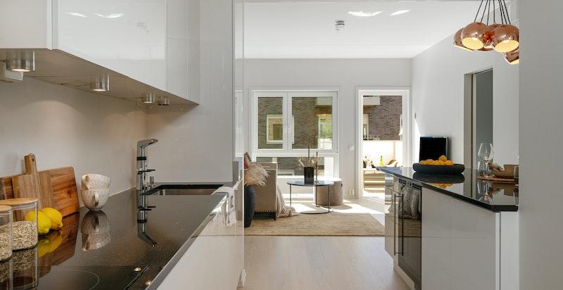 Kjøkken med integrerte hvitevarer som platetopp og stekeovn/oppvaskmaskin.