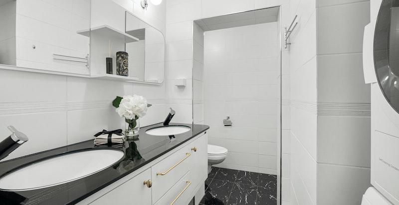 Pent flislagt bad med dobbeltservant, opplegg for vaskesøyle og romslig dusjnisje