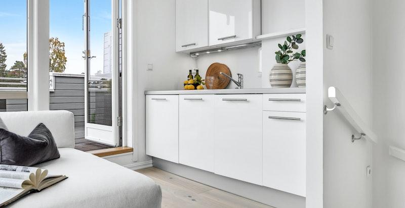 Loftet er innredet med kjøkken med glatte fronter og stålhåndtak, laminat benkeplater og stålkum med blandebatteri