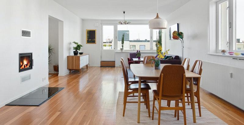 Peis med innsats er sentralt plassert i rommet og kan sees fra kjøkken, spisestue og sofadel