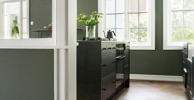 Vegg med glassruter deler spisestue og kjøkken