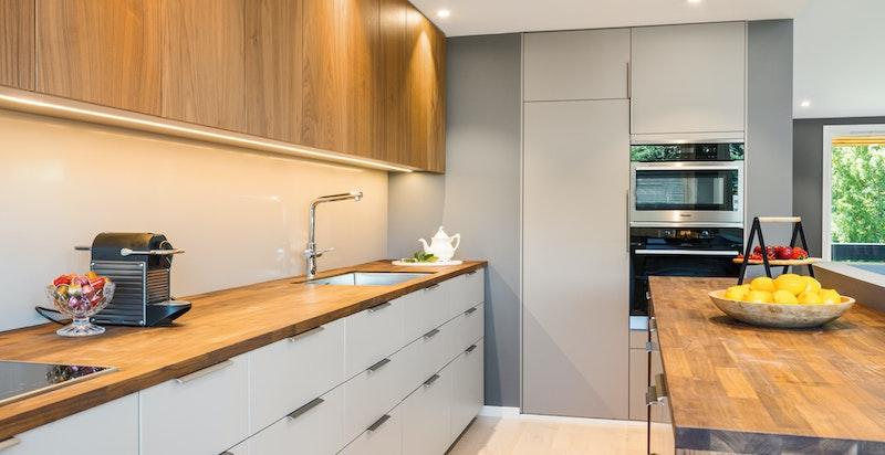 Kjøkken fra 2019 med delvis møbelsnekkret tilpasning. Skuffer og skap fra IKEA med valnøtt fronter og valnøtt benkeplater.