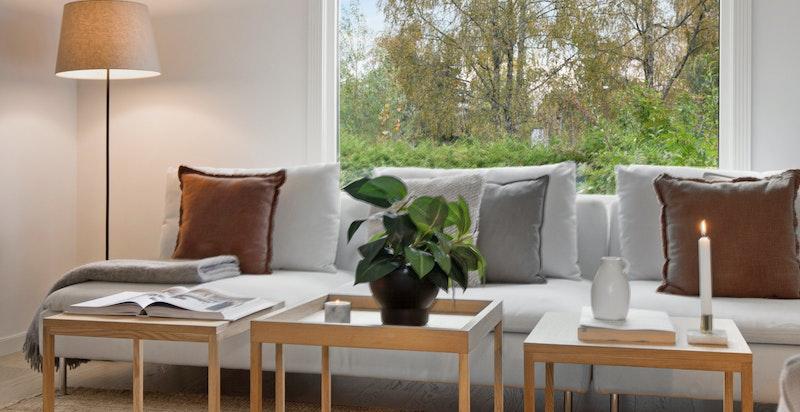 Nyoppusset stue med en-stav parkett og store vinduer som slipper inn mye lys.