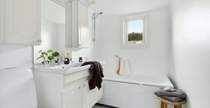 Flislagt bad med varmekabler utstyrt med gulvmontert wc, servantskap med skuffer/skap og frittstående badekar.