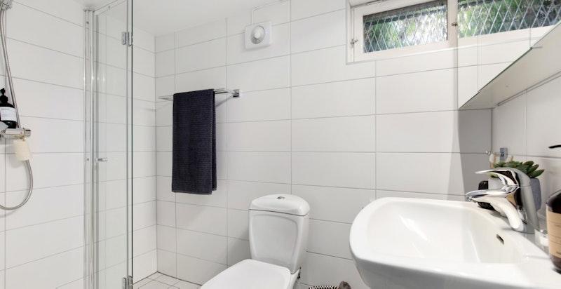 Flislagt bad med varmekabler utstyrt med gulvmontert wc, vegghengt servant med speilskap og dusjnisje med dører i herdet glass. Badet i kjeller er totalt oppgradert med nytt sluk og rør i rørsystem i 2016.