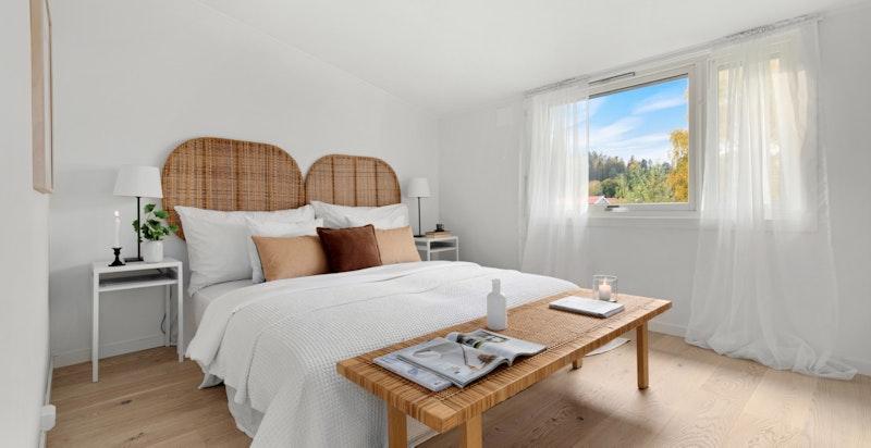 Lyst hovedsoverom av god størrelse med markise og god plass til dobbeltseng, tilhørende nattbord og oppbevaringsmøbler.