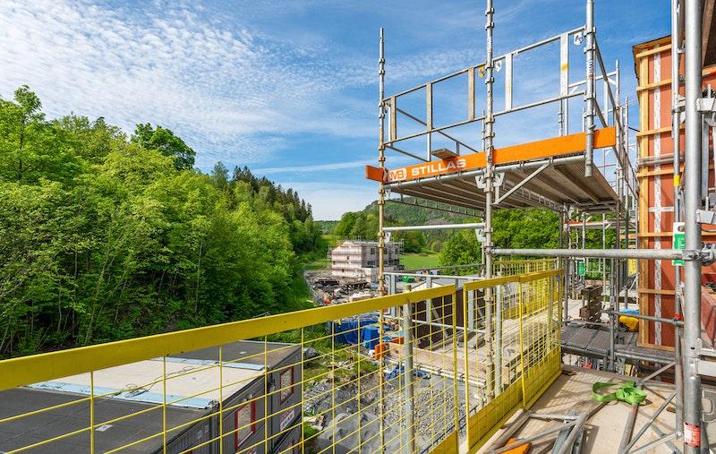 Utsyn fra balkong (brakker forsvinner slik at man ser skogen bak)
