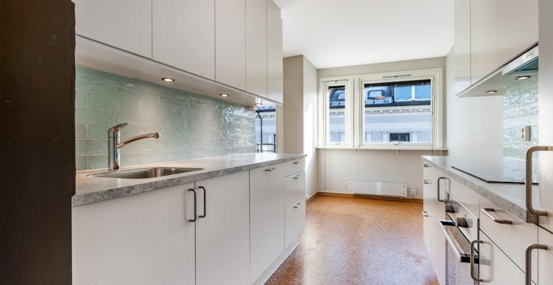 Kjøkken med integrerte hvitevarer og plass til spisebord
