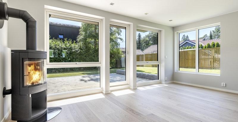 Romslig stue med peisovn og store vindusflater