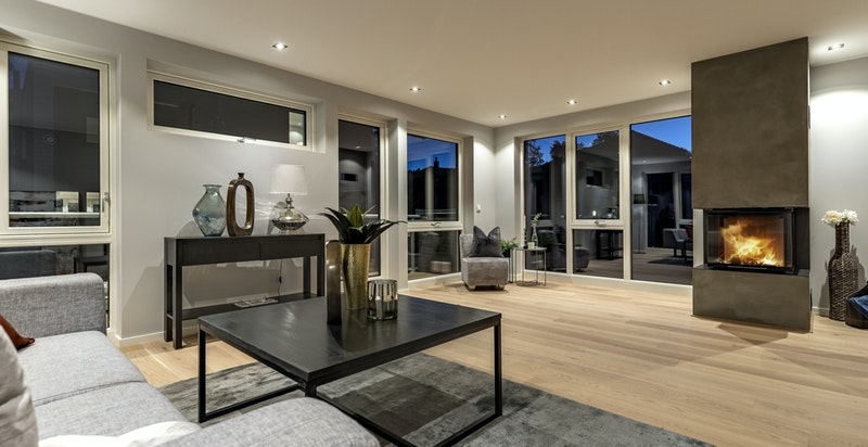 Stue med store vindusflater og peis