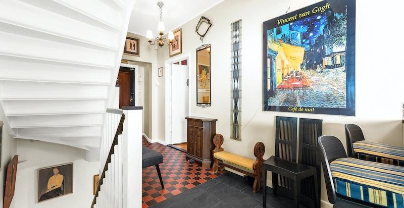 Entré/hall med sort- og rødfarget gulv med sjakkmønstrede fliser over elektrisk gulvvarme. Original hvitmalt trapp i trekonstruksjon med tette trinn, malte vanger, gelender og håndløper