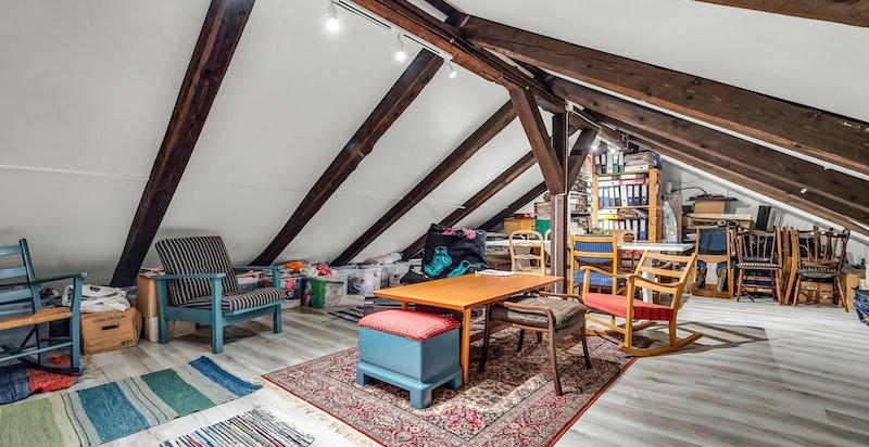 Loftet består av et stort lagringsareal med bjelker og stendere, takplater og laminatgulv