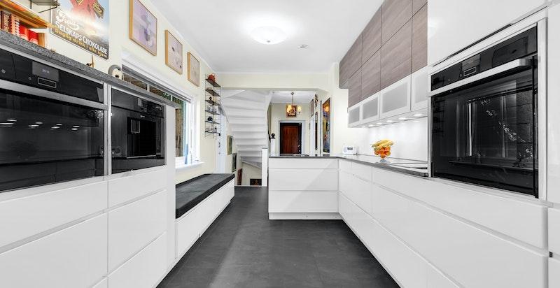 Innredningen har høyglansfronter på skuffer, underskap og høyskap, glassplater på vegg mellom benk og overskap, benkeplater i sort  granitt med skjulte stikkontakter, utrekkbart kjøleskap, underlimt oppvaskkum i sort kompositt.