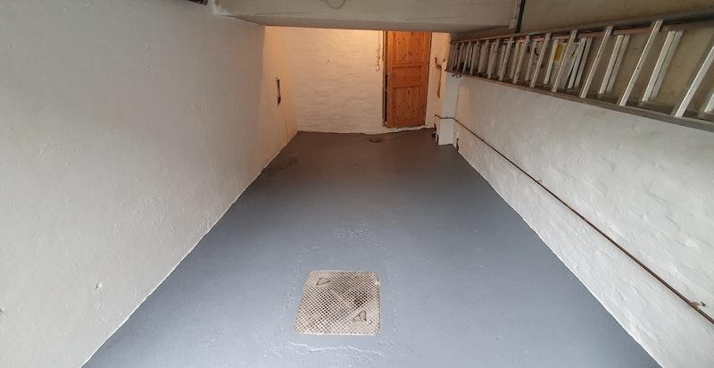 Det er garasje integrert i boligens kjeller. Garasjen har plass til én normal personbil. Det er adkomst (dør) fra garasjen inn til boligens kjelleretasje