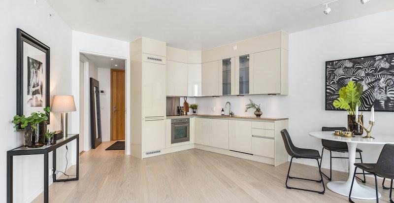 Kjøkkenet har beige høyglans fronter og heltre benkeplate.