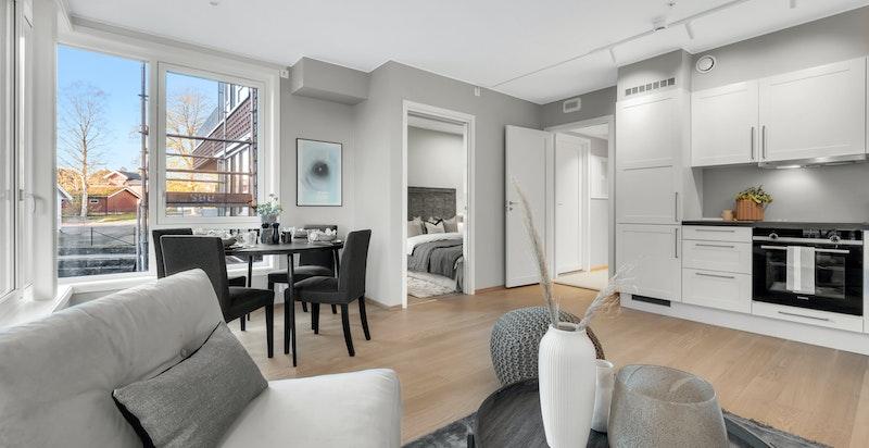 Stue med luftig og lys atmosfære. 2 hvite spotskinner hjelper på når mørket har senket seg ute.