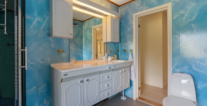 Badet er innredet med dobbelservant, dusjkabinett og toalett