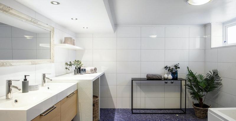 Meget romslig baderom med vaskesøyle, badekar med dusj, dobbelservant, vegghengt toalett. Varme i gulv.