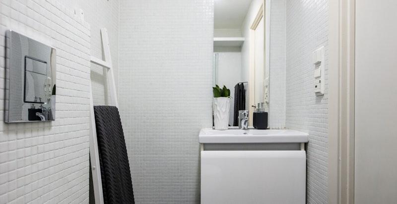 Hvite mosaikkfliser på alle veggflatene.
