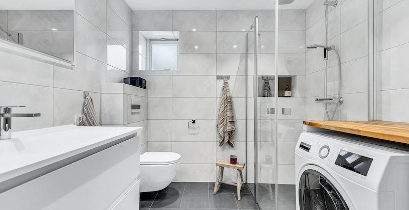 Lekkert bad fra 2017 innredet med dusjhjørne med innfellbare dusjdører, servant med underskap, veggmontert toalett. Opplegg til vaskemaskin