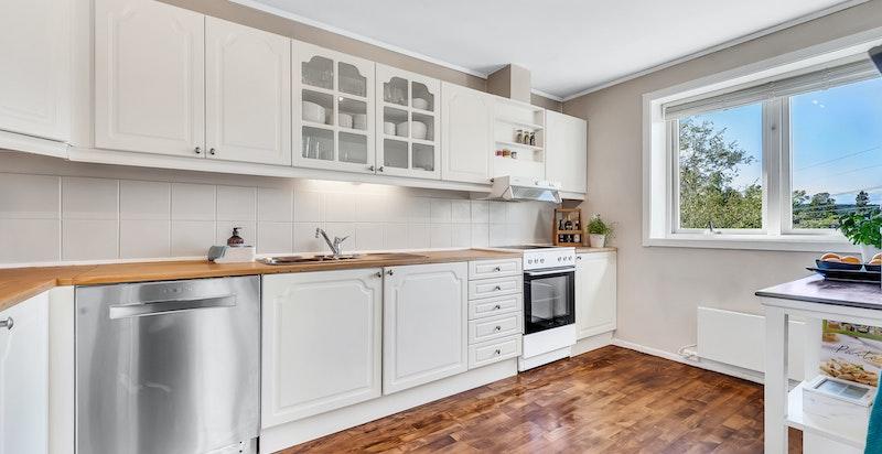 Kjøkken med innredning bestående av profilerte fronter med stålhåndtak, heltre benkeplater, to stålkummer med blandebatteri, fliser over benk og lys under overskap