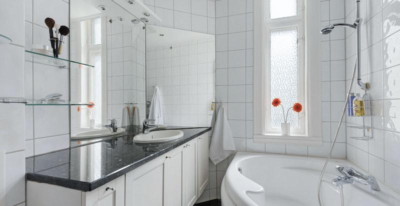 Delikat og romslig flislagt bad/wc med hjørnebadekar og vindu mot bakgård