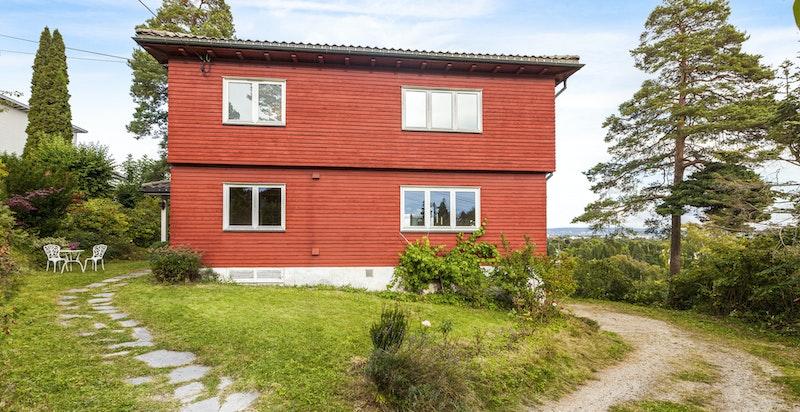 Fasade/tomt. Gressplen og prydbusker på alle sider av huset.