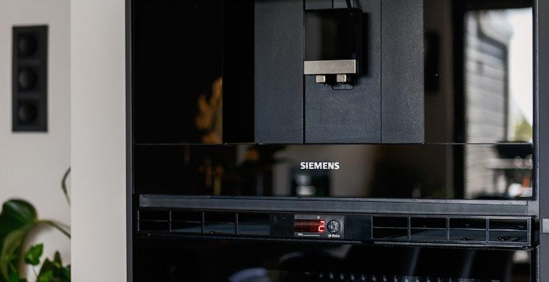 Kaffemaskin og vinskap montert i høyskap, det er også stekeovn og dampovn