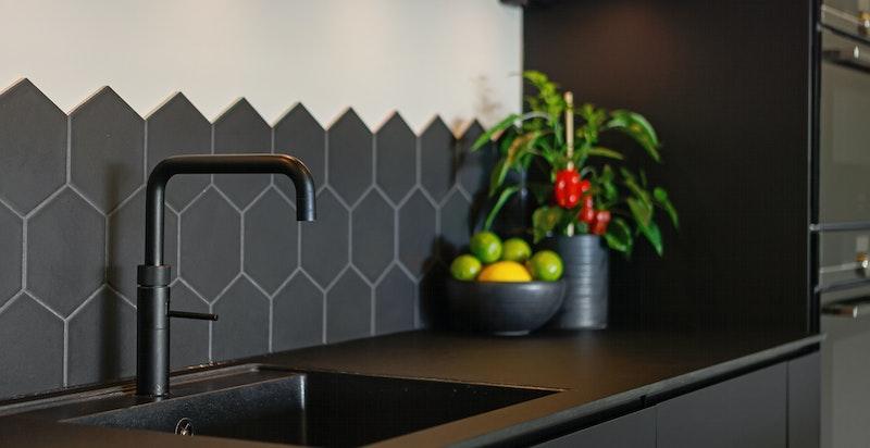 Sorte glatte fronter på skuffer og skap, med softclose. Det er hexagon fliser på vegg mellom oppvaskbenk og overskap. Det er montert kran fra Quooker som gir deg kokende vann på sekundet